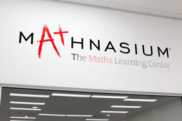 Close-Up Of Mathnasium Signage On A White Wall. Signage Reads: Mathnasium, The Maths Learning Centre. The Signage Lettering Is In Black, The Letter A And The Word Maths Are In Red Colour. Impeccabuild Fit Out Of Mathnasium In Hornsby On The Upper North Shore Of Sydney In The Australian State Of New South Wales. Interior Fit Out And Commercial Fit Out.