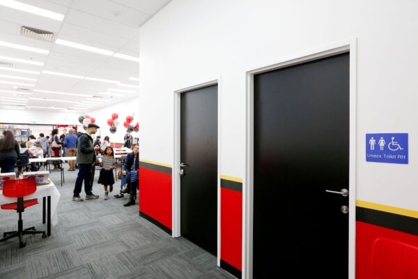 Mathnasium, The Maths Learning Centre. Grand Opening Day, With Numerous People Inside The New Shop. Walls Are Painted In The Mathnasium Colour Scheme Of Red Sections, With A Black And Yellow Strip And White Upper Section. Grey Carpet Tiles, White Acoustic Ceiling Tiles, LED Light Panels In The Ceiling Grid And Two Doors Painted Black. Impeccabuild Fit Out Of Mathnasium In Hornsby On The Upper North Shore Of Sydney In The Australian State Of New South Wales. Interior Fit Out And Commercial Fit Out.