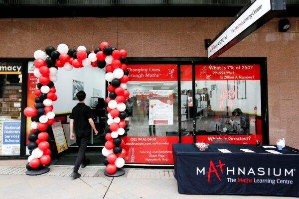 Mathnasium, The Maths Learning Centre. Grand Opening Day At Hornsby Nsw. The Shopfront With The Mathnasium Signage, In The Colours Of Red Black And White. A White Signage Lightbox, Glazing Signage, Multicoloured Balloons And A Black Table Outside For Promotional Purposes. Numerous People Inside The Shop Celebrating The Opening Of The Learning Centre. Interior Fit Out By Impeccabuild For Mathnasium In Hornsby On The Upper North Shore Of Sydney In The Australian State Of New South Wales. Interior Fit Out And Commercial Fit Out.