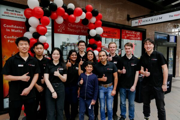 Mathnasium, The Maths Learning Centre. Grand Opening Day At Hornsby NSW. The Staff Are Seen Here Smiling With Their Thumbs Up Outside The Shopfront. Red, Black And White Balloons In The Background, The Mathnasium Shopfront Signage, And Lightbox. Interior Fit Out By Impeccabuild For Mathnasium In Hornsby On The Upper North Shore Of Sydney In The Australian State Of New South Wales. Interior Fit Out And Commercial Fit Out.