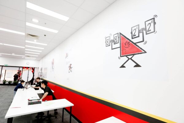 Mathnasium, The Maths Learning Centre. Walls Are Painted In The Mathnasium Colour Scheme Of Red Sections, With A Black And Yellow Strip And White Upper Section. Grey Carpet Tiles, White Acoustic Ceiling Tiles, Led Light Panels In The Ceiling Grid And Two Doors Painted Black. Two Staff And Teachers Are Sitting At White Desks Reviewing Papers, Numerous Signages On The Walls With Animated Figures. Interior Fit Out By Impeccabuild For Mathnasium In Hornsby On The Upper North Shore Of Sydney In The Australian State Of New South Wales. Interior Fit Out And Commercial Fit Out.