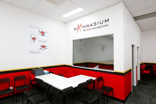 Mathnasium Learning Centre Fit Out In Hornsby, North Shore Sydney New South Wales. Interior Fit Out By Impeccabuild. Office Equipment, Two White Tables, Numerous Black And Red Office Chairs, Grey Carpet Tiles, hite Ceiling Tiles and Grid, Wall Paint In Mathnasium Colour Scheme, Red Bottom Section Of Wall Paint, Black And Yellow Strip And White Paint To The Top Section Of The Wall, Printer On The White Table, Glazing for the Office and Admin room, Signage Animated Figures On The Walls. Fit Out By Impeccabuild Experts From Sydney.